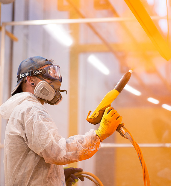 Skilled technician from a powdercoating services company powder coating