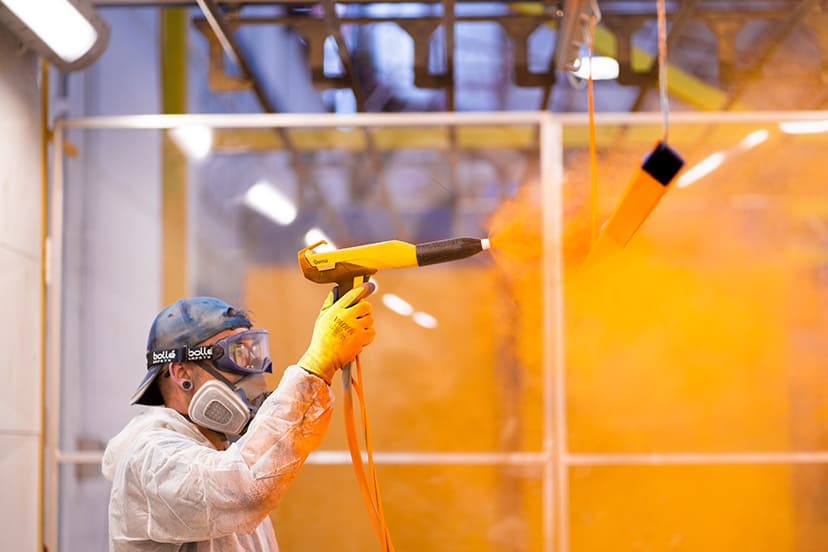 Man from a perth powdercoating services team powdercoatng a piece of metal