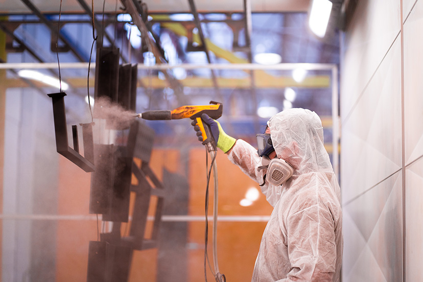 Technician from a perth powdercoating services company powdercoatng a piece of metal