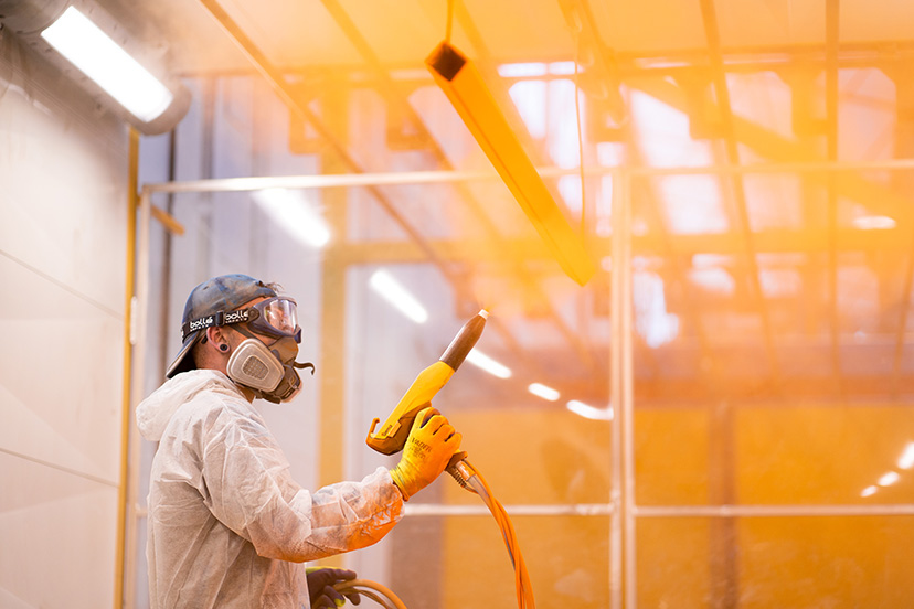 Technician from a powdercoating perth team powdercoatng a piece of metal